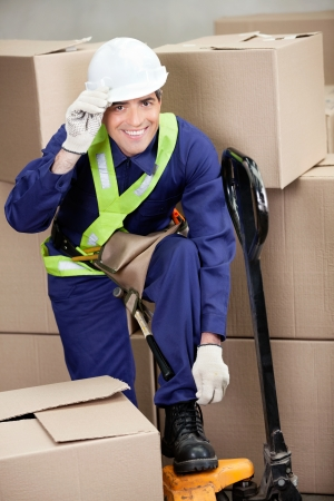 Portrait of mid adult foreman with fork pallet truck in warehouse photo