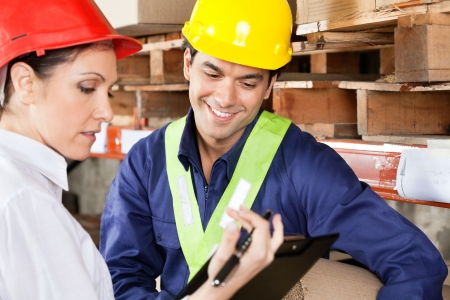 Female supervisor showing clipboard to young foreman at warehouse Stock Photo - 16120089