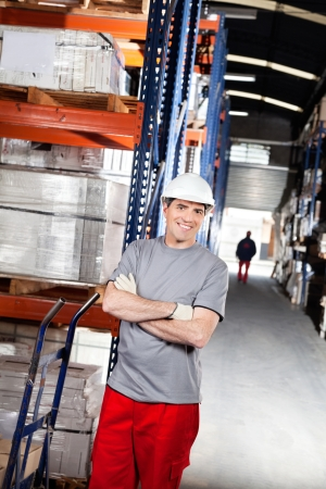Portrait of smiling warehouse worker with handtruck at warehouse photo