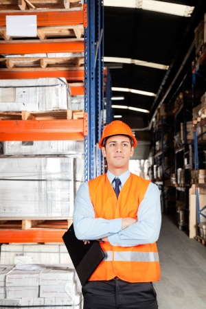 Confident young male supervisor in orange protective vest with arms crossed at warehouse Stock Photo - 16120067