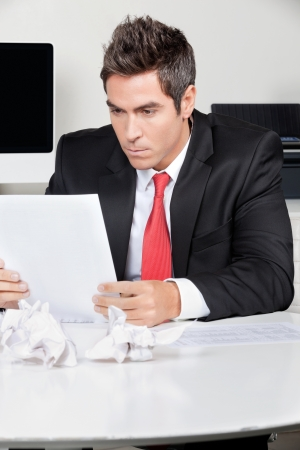 Young businessman reading document at desk in office photo
