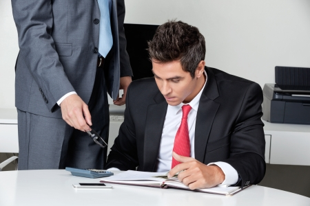 concentrating: Two businessmen calculating finances at desk in office Stock Photo