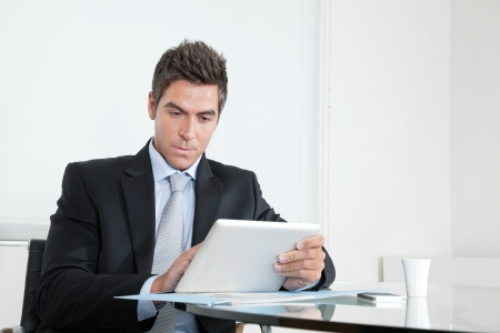 Handsome young businessman at desk with digital tablet and coffee cup in office Stock Photo - 16155483