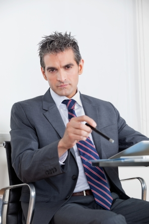 Portrait of mid adult businessman with digital tablet at desk in office Stock Photo - 16155498