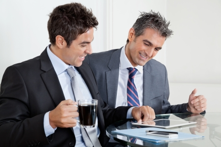 Two happy businessmen using digital tablet at desk in office Stock Photo - 16155265