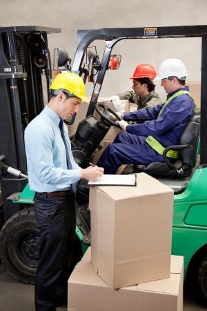 lift truck: Supervisor por escrito en el portapapeles con los capataces de trabajo en el almac�n