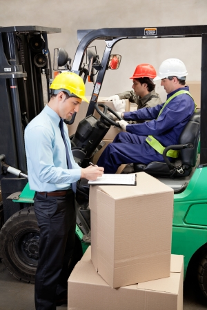 forklift driver: Supervisor writing on clipboard with foremen working at warehouse