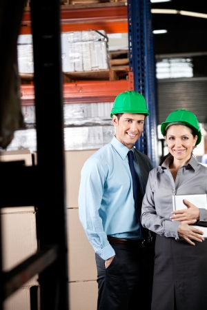 Portrait of two young supervisors with digital tablet smiling together at warehouse Stock Photo - 16155375