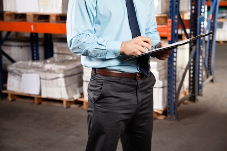 Midsection of male supervisor writing on clipboard at warehouse Stock Photo - 16155776