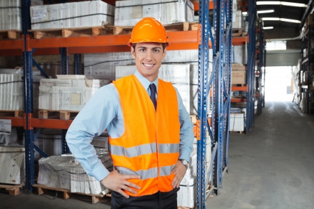 warehouse equipment: Portrait of confident young supervisor standing at warehouse
