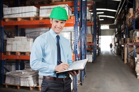 Portrait of confident young supervisor with book standing at warehouse photo