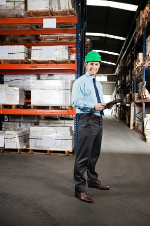 Portrait of confident young supervisor with clipboard standing at warehouse photo