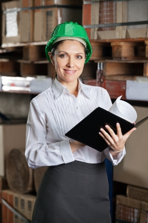 Portrait of confident young female supervisor with book standing at warehouse photo