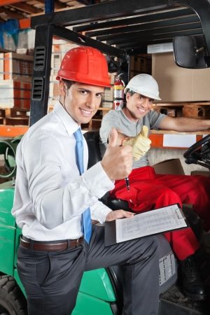 Portrait of supervisor and forklift driver gesturing thumbs up at warehouse photo