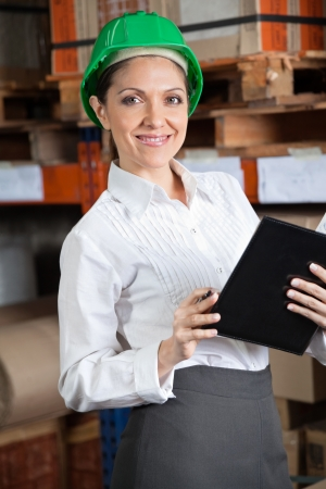 Portrait of young female supervisor with book standing at warehouse photo