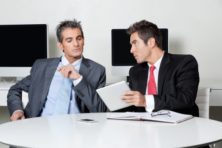 Two businessmen using digital tablet at desk in office Stock Photo - 16191649