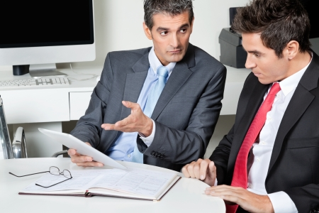 Two businessmen using digital tablet at desk in office Stock Photo - 16191678