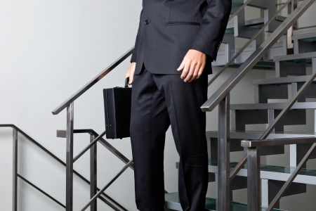 descending: Low section of young businessman walking down the stairs at office