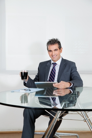 Portrait of mid adult businessman with coffee cup using digital tablet at desk in office Stock Photo - 16191652