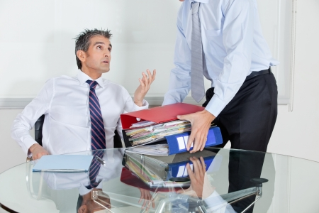 Mid adult businessman at desk overwhelmed by load of work Stock Photo - 16191654