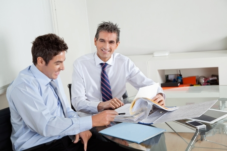 Portrait of mid adult businessman with colleague discussing paperwork at a meeting in office Stock Photo - 16191667