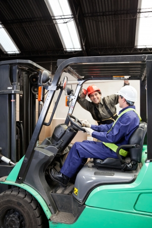 Forklift driver communicating with colleague at warehouse photo