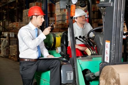 Man begeleider met klembord instrueren heftruckchauffeur in het magazijn,
