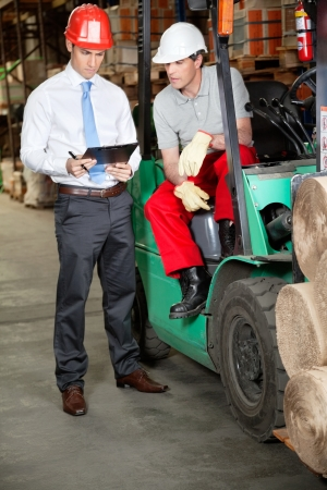 Forklift driver and supervisor working in warehouse photo
