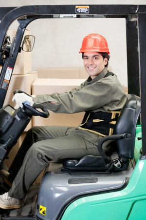 forklift driver: Portrait of young confident forklift driver at warehouse Stock Photo