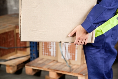 Midsection of young foreman in uniform carrying cardboard box at warehouse photo