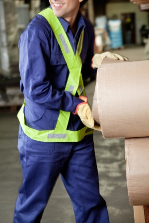 Midsection of young foreman in uniform working at warehouse photo