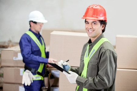 Portrait of young supervisor writing notes clipboard while foreman working at warehouse photo