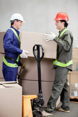 man carrying box: Two foremen lifting cardboard box at warehouse Stock Photo