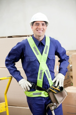 Portrait of a confident foreman in protective clothing standing in warehouse photo