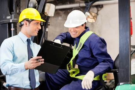 foreman industrial: Supervisor showing clipboard to forklift driver at warehouse