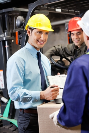 Young male supervisor showing clipboard to mid adult foreman at warehouse photo