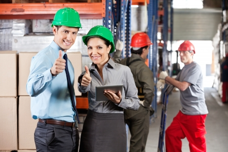 Portrait of supervisors with digital tablet gesturing thumbs up with workers in background photo