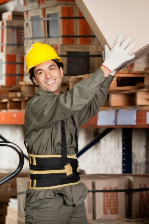 Happy foreman lifting a cardboard box at warehouse photo