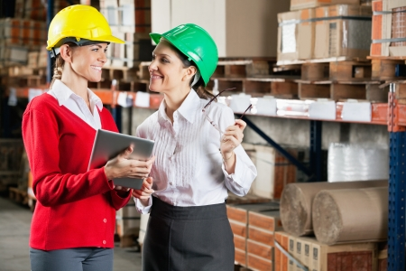 Two female supervisors with digital tablet discussing work at warehouse photo