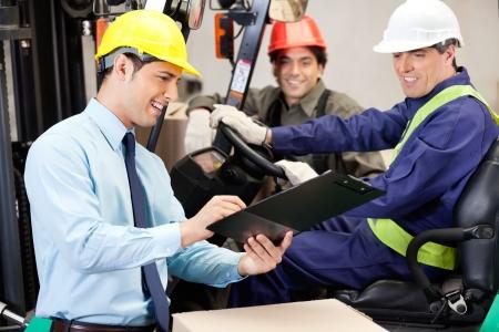 supervisores: Supervisor de feliz hombre comunicarse con conductor de carretilla elevadora y capataz en almac�n