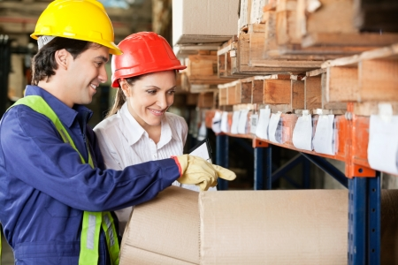 Young foreman and female supervisor checking stock at warehouse Stock Photo - 16191670