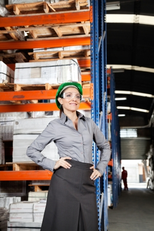 Young female supervisor wearing protective eyeglasses with hands on hips at warehouse photo