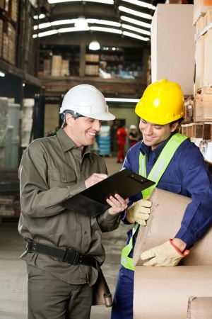Supervisor showing clipboard to young foreman at warehouse photo
