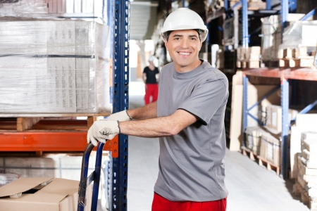 Portrait of warehouse worker pushing handtruck with cardboard boxes at warehouse photo