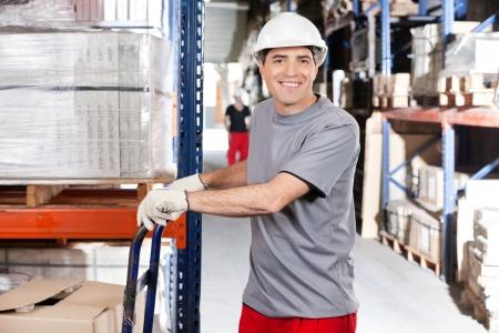 empujando: Retrato del trabajador del almac�n carretilla empujando con cajas de cart�n en el almac�n