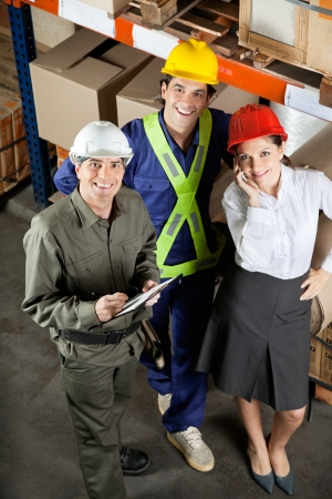 High angle portrait of young foreman with supervisors smiling together at warehouse photo