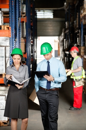 Female supervisor with colleague working at warehouse with foreman unloading cardboard boxes photo