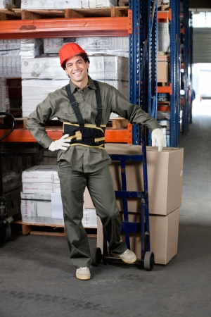 Portrait of young foreman with handtruck loading cardboard boxes at warehouse photo