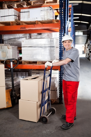 Portrait of warehouse worker with handtruck loading cardboard boxes at warehouse photo