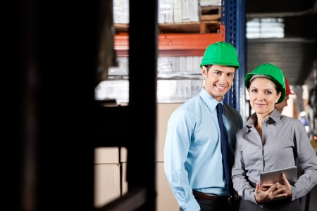 Portrait of two young supervisors with digital tablet smiling together at warehouse photo